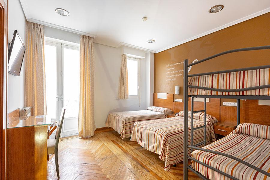 Habitación cuádruple Hostal Abadía Madrid centro con camas individuales y litera