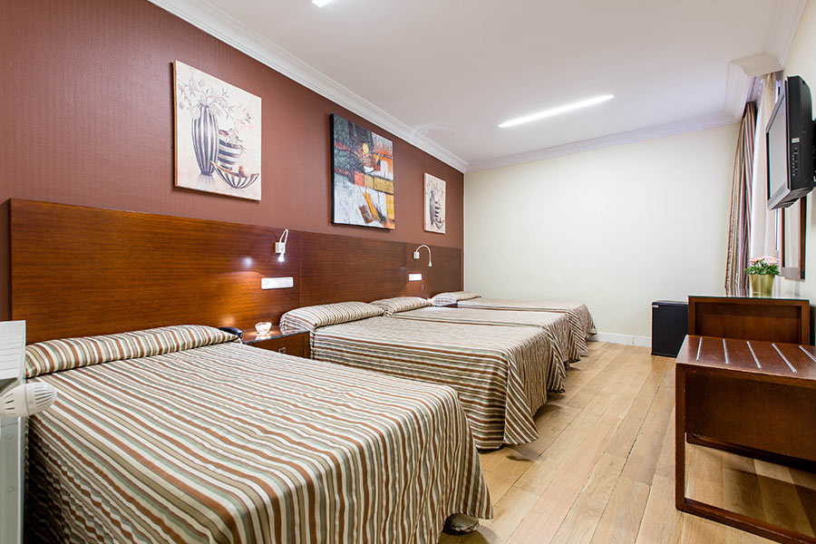 Habitación cuádruple Hostal Abadía Madrid centro con cuatro camas individuales