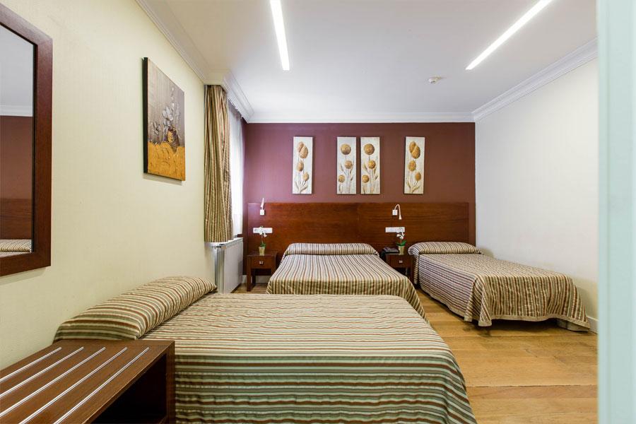 Habitación triple Hostal Abadía Madrid centro formato dos camas dobles y una amplia