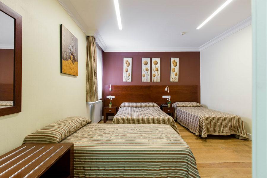 Habitación triple Hostal Abadía Madrid centro con formato dos camas dobles y una individual
