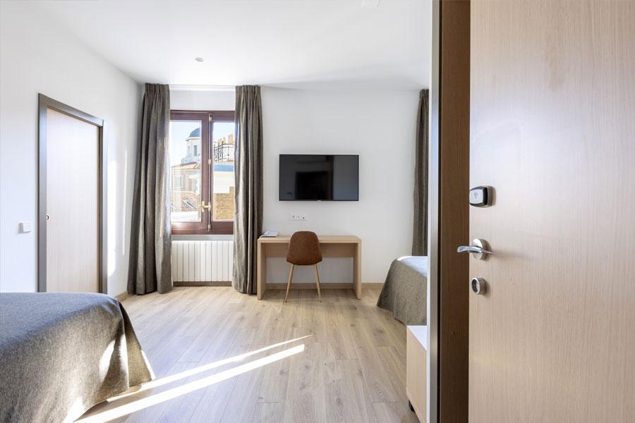 Habitación triple Hostal Abadía Madrid centro con escritorio y TV