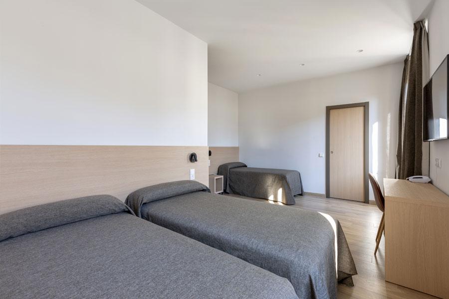 Habitación triple Hostal Abadía Madrid centro en formato dos y uno con escritorio